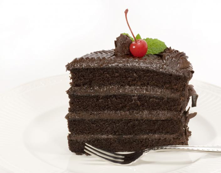 [Image: Layered chocolate cake with a cherry on top]